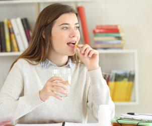 wanita sedang minum suplemen maitake